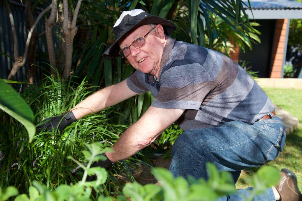 Older male in blue shirt & glasses smiling watering garden