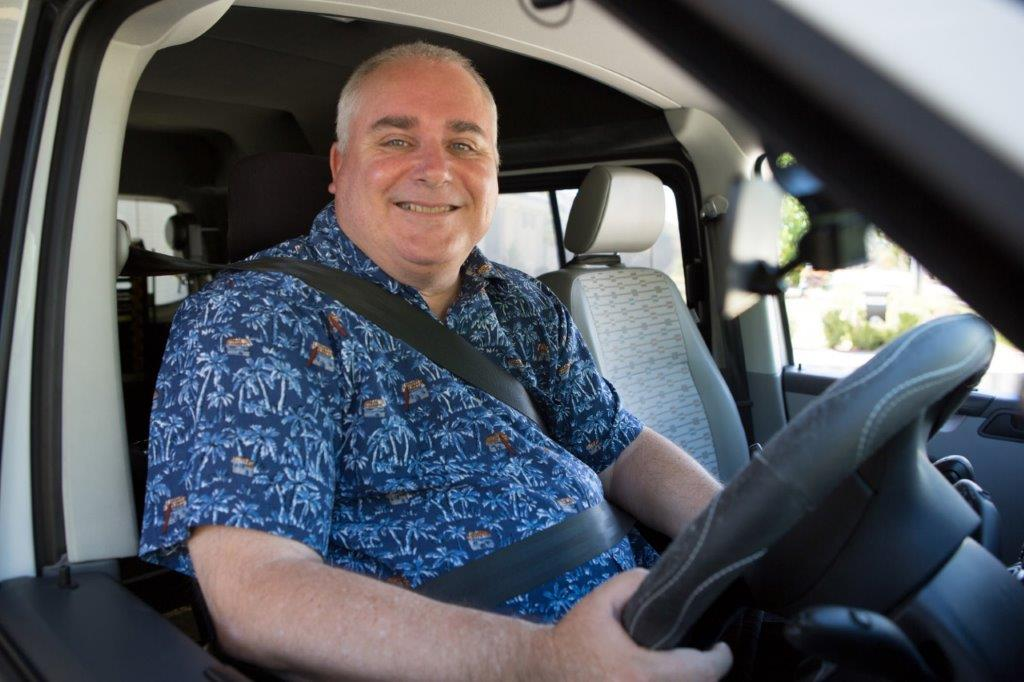 Man smiling in the driver's seat of a car