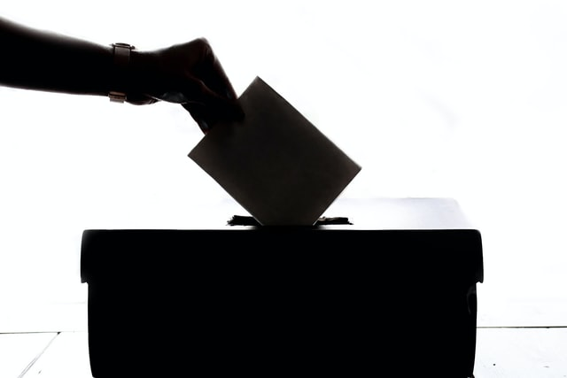 Silhouette of hand placing a vote into a voting box