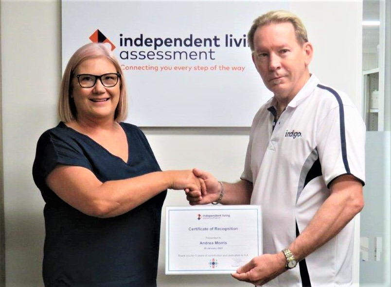 Professional female with glasses shaking hand of professional male who's holding a certificate in front of ILA sign