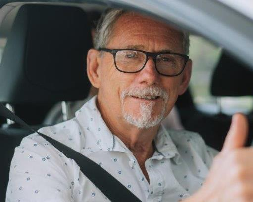 Older male with a beard, wearing glasses giving a thumbs up from inside a car