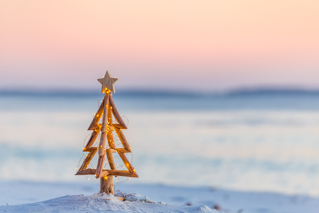 blurred image of a beach sunset with metal Christmas in foreground